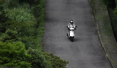 Photo of a woman driving a moped down the road near Yangmingshan National Park in Taipei.