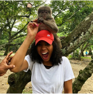 Vanessa with a monkey sitting atop her shoulders and head