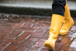 A picture of a woman wearing yellow rain boots walking on a red brick pathway on the University of Washington campus.